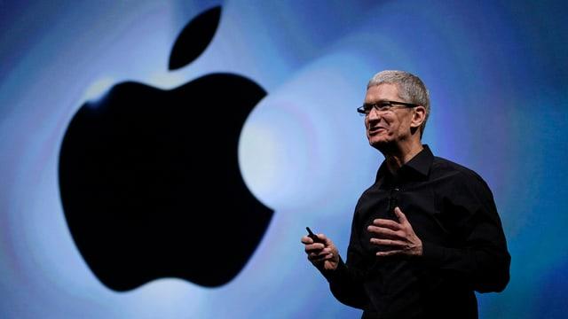Tim Cook vor Apple-Emblem