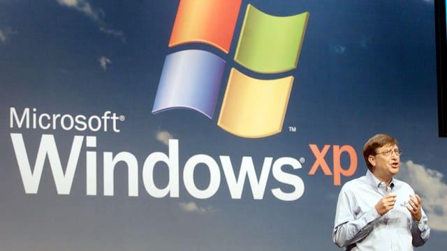 Der ehemalige Microsoft-Chef Bill Gates steht gestikulierend vor einem grossen Windows-XP-Logo.