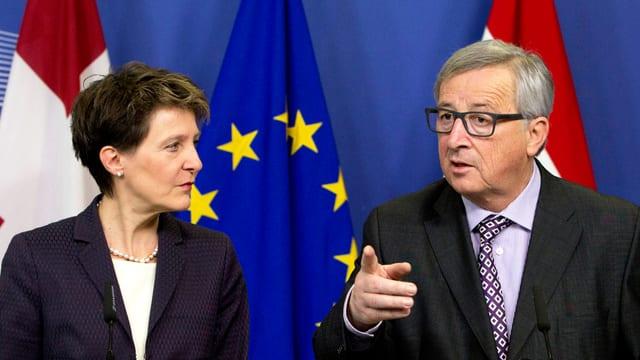 Zwei Politiker bei einer Pressekonferenz vor einer Europa- und Schweizerflagge.