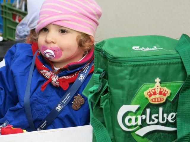 Kind mit Nuggi, daneben Carlsberg-Kühltasche