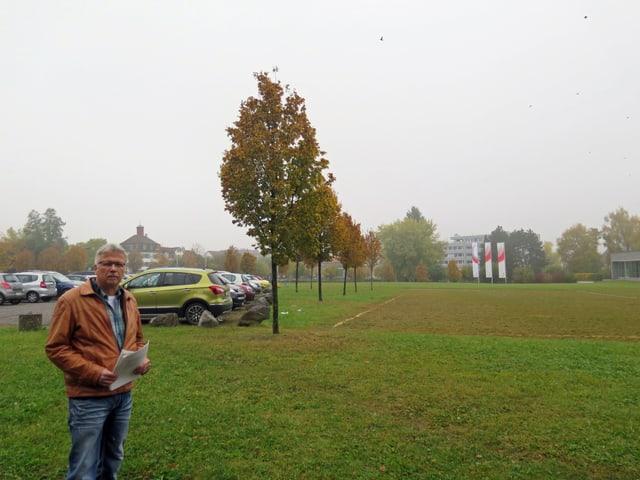 Ernst Zülle steht links im Bild, rechts eine grüne grosse Wiese