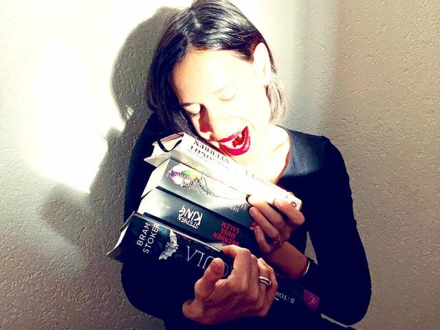 Annette König beisst mit ihren Vampirzähnen in einen Stapel Vampirbücher