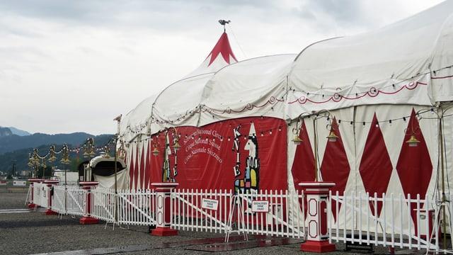 Weisses Zirkuszelt des Cirkus Knie mit roten Mustern darauf.
