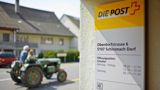 Das Eingangsschild der Posstelle Schinznach Dorf. Im Hintergrund fährt ein grüner Traktor