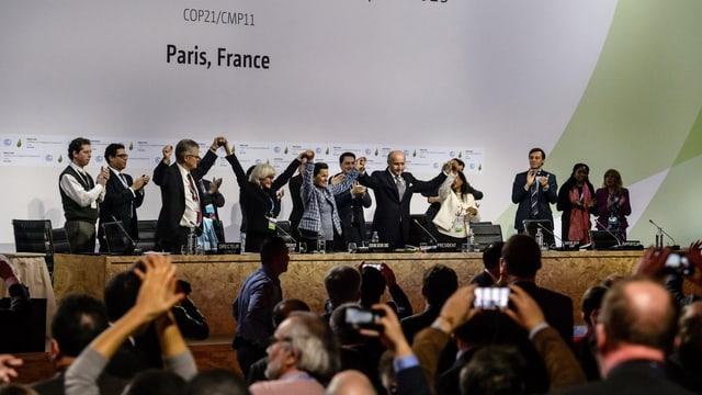 Blick in den Konferenzraum in Paris: Gäste applaudieren nachdem die Verantwortlichen die Einigung bekanntgegeben haben.