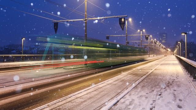 """Verschneite Wettsteinbrücke in Basel. Nur das """"Trämli"""" ist grün."""