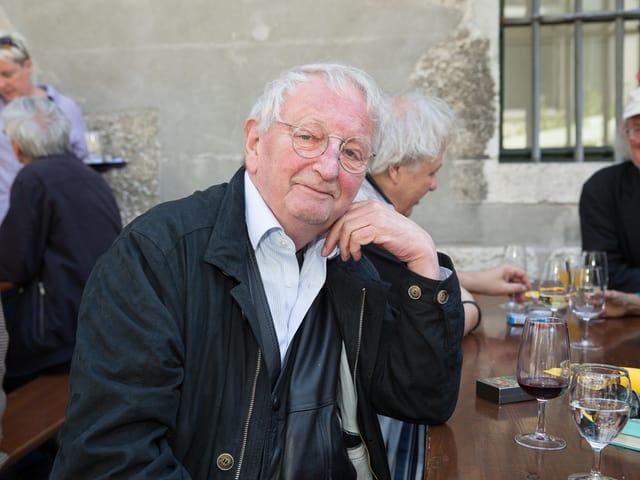 Peter Bichsel sitzt mit einem Glas Wein an einem Tisch.
