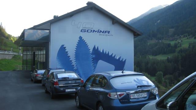 Ein Gebäude an einem Talhang, daneben stehen Autos.