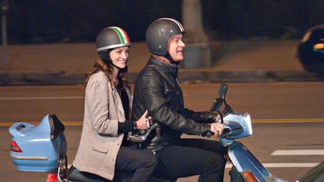 Eine Frau und ein Mann fahren auf einem Roller.