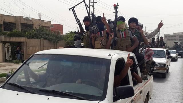 Kämpfer des Islamischen Staats in Siegerpose auf einem Pick-up-Fahrzeug.