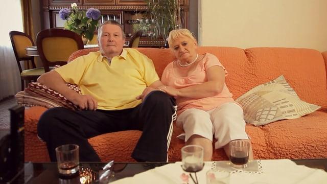 Ein Paar sitzt auf einem Sofa und schaut in die Kamera.