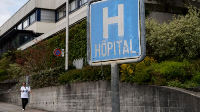 Blaues Spitalschild mit französischer Aufschrift «Hôpital» vor Spitalgebäude.