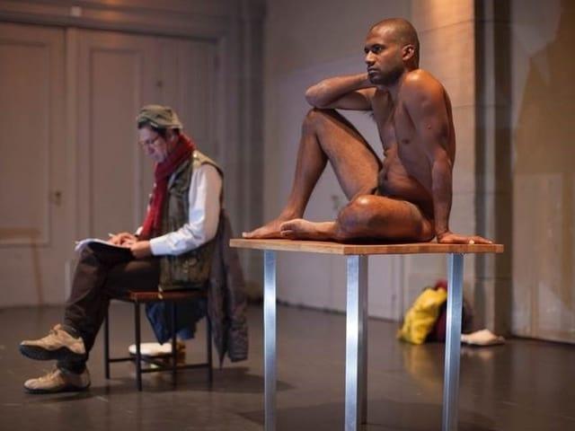 Links: Mann mit rotem Schal auf Stuhl, rechts: Nachter Mann mit dunkler Haut auf Tisch.
