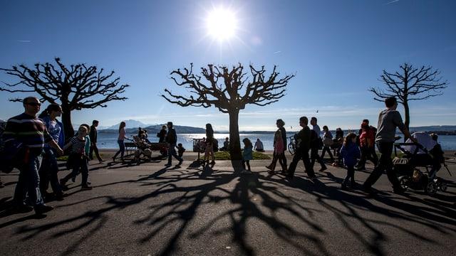 Spaziergänger geniessen das sonnige Wetter am Zugersee.