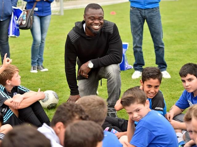 Asamoah kniet sich lachend vor einer Schar Kinder.