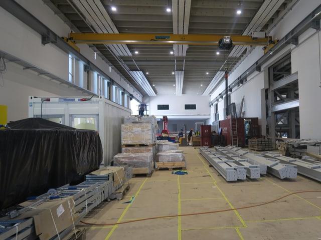 Fabrikhalle mit verschiedenen Metallelementen am Boden.