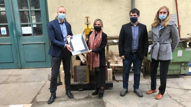 Vier Personen bei der Übergabe eines Urkunde.