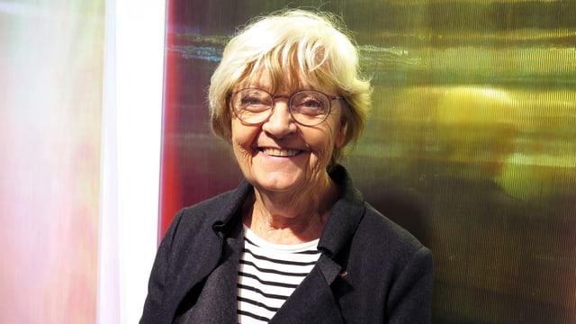 Eine Frau mit Brille vor zwei monochromen Bildern.