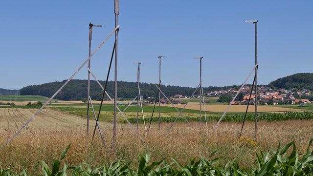 Baugespann auf Feld, im Hintergrund Dorf