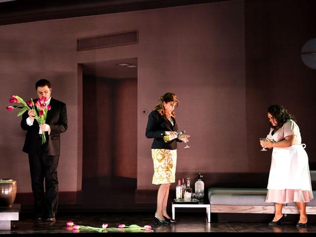 Zwei Frauen und ein Mann auf der Bühne, die ein Hotelzimmer darstellt.
