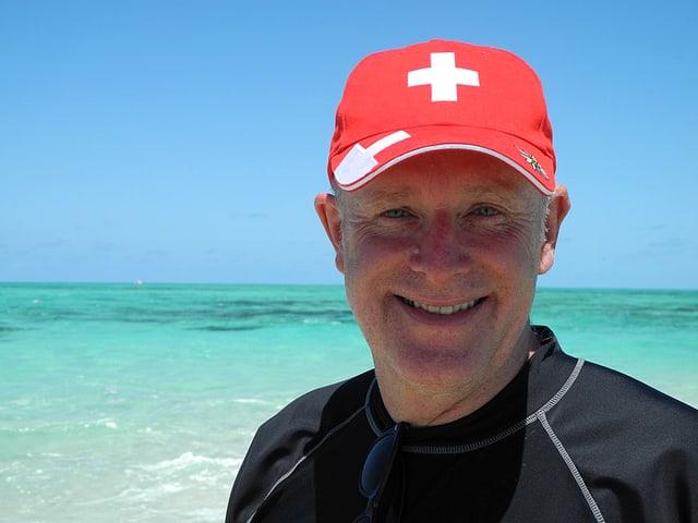 Urs Wälterlin mit Schweizer-Kappe am Meer.