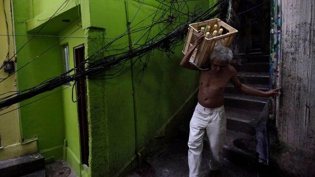 Älterer Mann trägt eine Kiste mit Getränken über eine schmale Treppe.