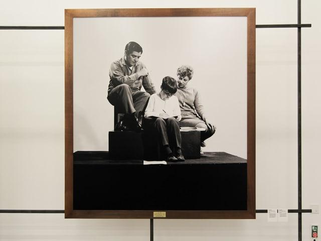Eine Familie sitzt auf einem Sockel und ist Teil einer Ausstellung.