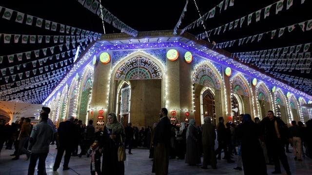 Mit Lichtern dekorierte Moschee in Bagdad, Menschen davor
