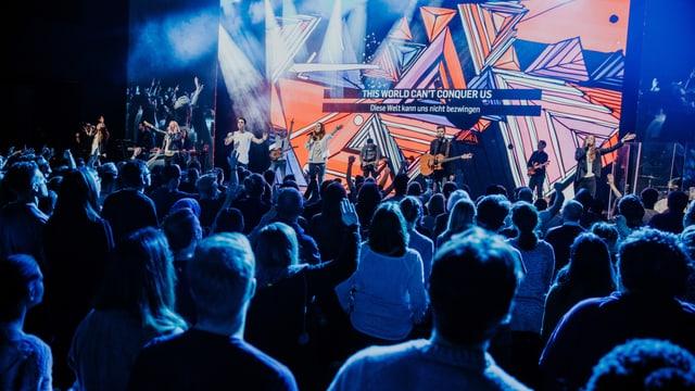 Publikum vor Musikbühne, darauf eine Band in blauem Licht