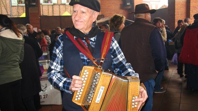 Auf dem Markt: ein alter Mann mit Béret, Karo-Hemd und Akkordeon