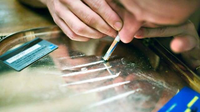 Durch eine gerollte Hunderternote wird Kokain geschnupft.