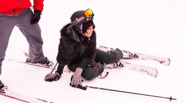 Sängerin Rihanna liegt mit Skiern am Boden.