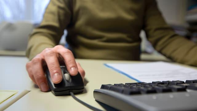 Ein Mann sitzt vor einem Computer, mit der rechten Hand führt er eine Maus.