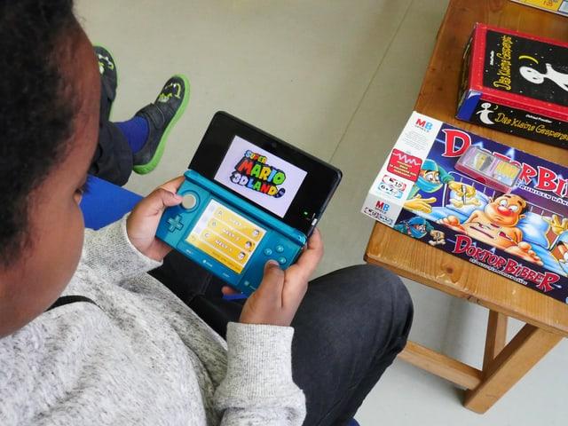 Ein Kind spielt mit einer Nintendo-DS-Spielkonsole, im Hintergrund ist sind die Brettspiele «Dr. Bibber» und «Das kleine Gespenst» zu sehen.