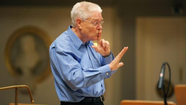 Der Dirigent Hans Zender hält bei den Proben einen Finger von dem Mund.