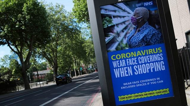 Ein Plakat der englischen Gesundheitsbehörde NHS, das zum Tragen von Hygienemasken auffordert.