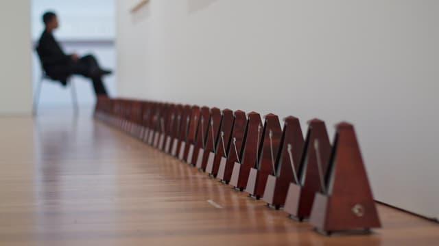 Eine Reihe von Metronomen in einer Kunstausstellung.