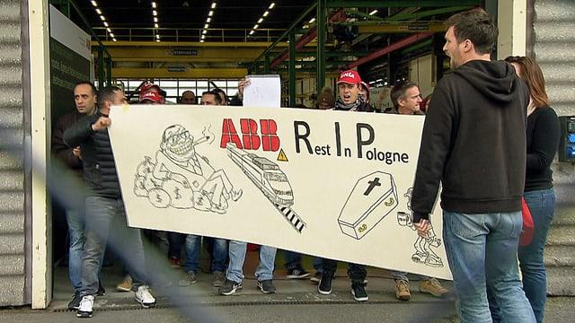 Protestierende Arbeiter mit einem Transparent.