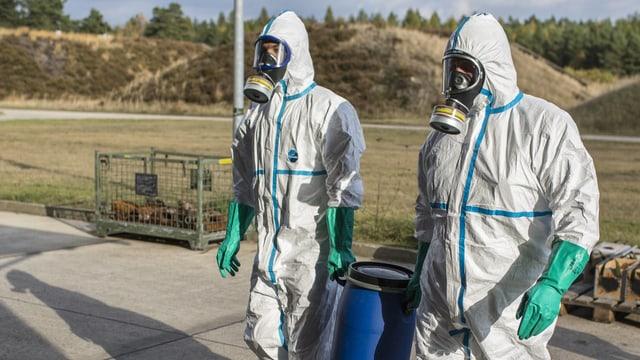 Symbolbild: Zwei Personen in Schutzanzügen und Gasmasken mit einem blauen Plastikfass.