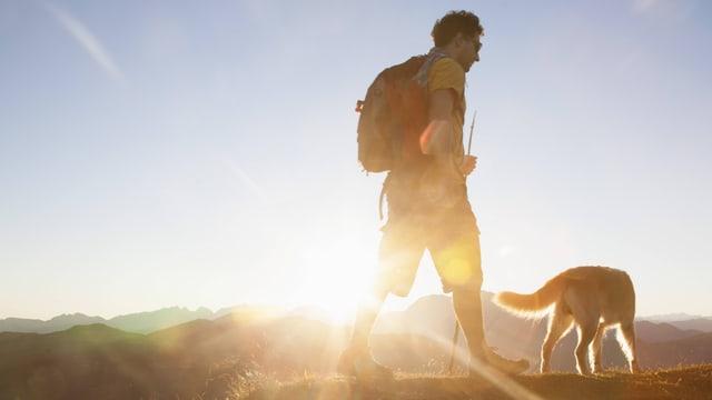 Ein Mann wandert mit seinem Hund.