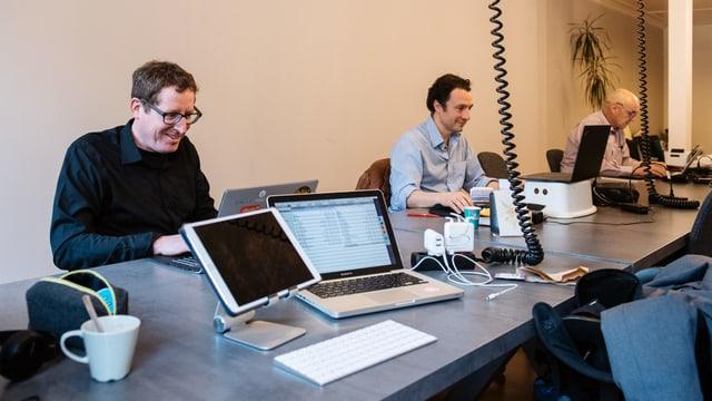 Drei Männer sitzen an einem langen Tisch vor ihren Laptops.