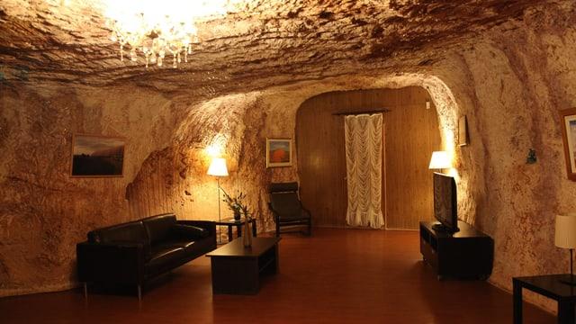 Wohnzimmer in einer Höhle mit Sofa und Fernseher