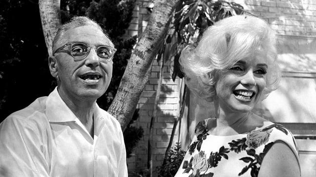 Eine Mann und eine blonde Frau lächeln.