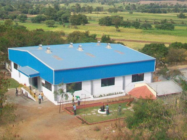 Blick auf die Vigyan Ashram Schule: Ein kleineres Haus, umgeben von Feldern.
