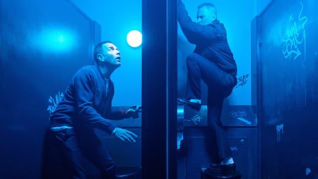 Zwei Männer sind auf einer öffentlichen Toilette