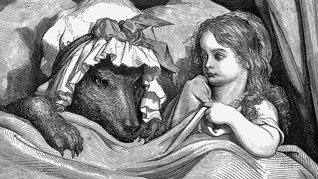 Der Wolf als Grossmutter verkleidet liegt mit Rotkäppchen unter der Bettdecke.