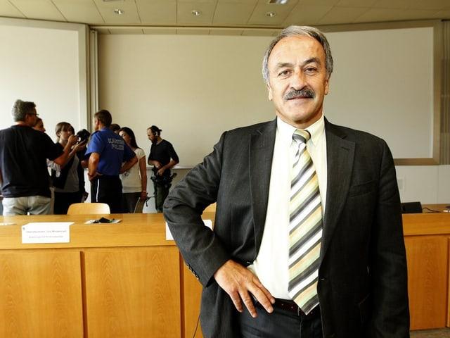 Mann mit Krawatte und schwarzem Jackett steht vor braunem Pult.