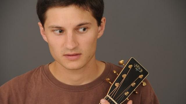 Der tschechische Liedermacher Jan Repka hät seine Gitarre im Arm.