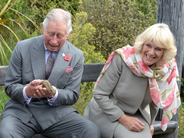 Charles eine Echse in der Hand haltend. Camilla sitzt daneben. Beide lachen.
