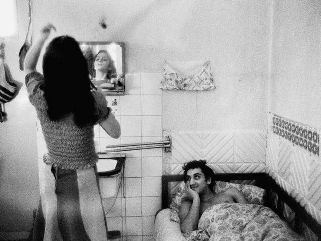 In einem kleinen Zimmer steht eine Frau vor dem Spiegel, ein Mann liegt daneben im Bett und schaut lächelnd zu.